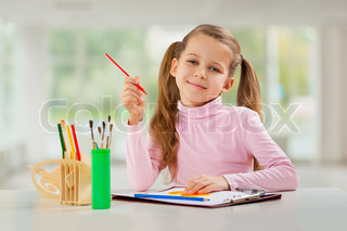 a young girl with pencil sitting at table