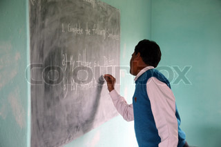 Teacher writes on blackboard at school in Kumrokhali, West Bengal, India