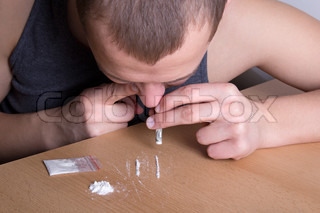 addicted man snorting heroin from the table