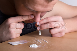 addict snorting heroin from the table