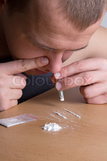 addict snorting heroin with dollar from the table