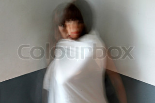 schizophrenic woman standing in a corner