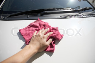 Hand cleaning a white car.