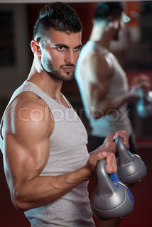 Young Men Lifting Kettle Bell In Gym