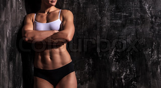 Muscled woman against a grunge background