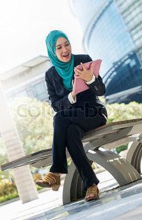 Young pretty business woman wearing scarf playing with a tablet touch pad computer gadget