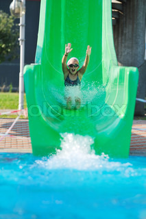Happy Girl Have Fun On Water Slide At Outdoor Swimming Pool Stock Photo Colourbox