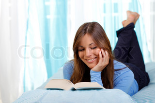 Woman in bed is reading a book