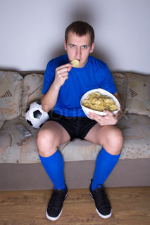 supporter watching football on tv at home and eating chips
