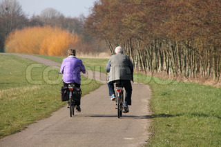 Happy couple, man and woman, she with pannier, are biking in spring in this park.