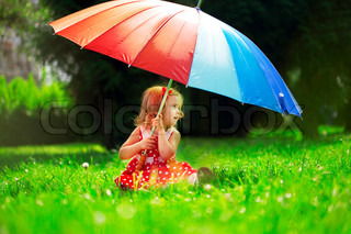 Little girl with a rainbow umbrella in park