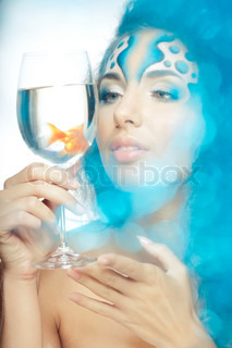 Girl with makeup, with a fish in a glass in her hand