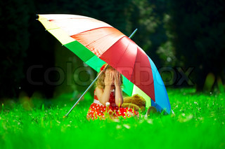Little girl hid in a park under a rainbow umbrella