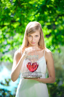 Sad woman with a heart in a cage