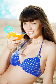 Beautiful woman with a drink in hand on the beach