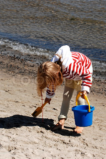 A girl collecting shells from a beach