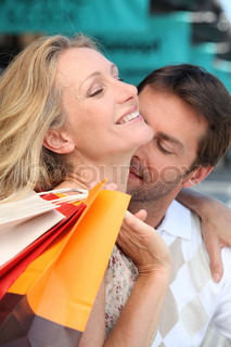 Man tenderly kissing her wife in the neck