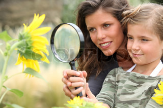 Young mum and daughter looking at a sunflower through a magnifying glass