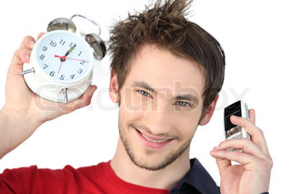 Man holding alarm clock and mobile