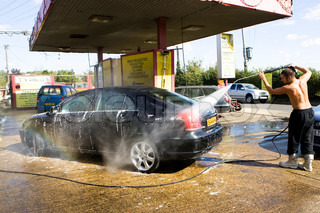 A man working in a hand car wash