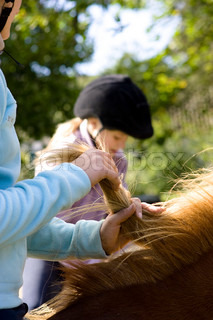 A female teenage rider holding the mane of her horse