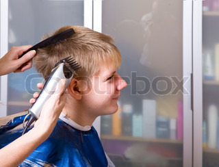 The happy teenager in hairdresser's salon