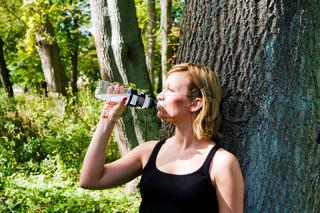 Ung kvinde lænet mod et træ og drikkevand