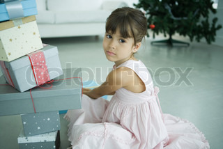 A young girl with a pile of Christmas presents