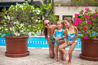 Little happy girls and young mother have fun near open-air pool