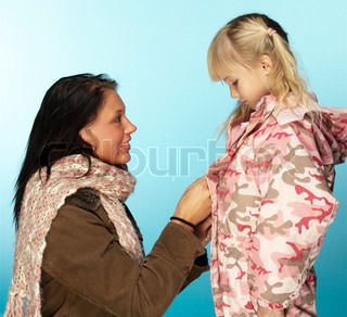A young girl gets help in putting on a winter jacket