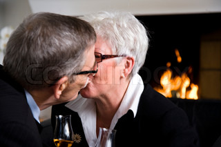 An elderly couple kissing on the lips