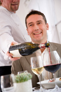 A waiter pouring red wine in front of his male guest