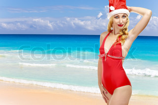 The girl in a bathing suit and a cap of Santa Claus and ocean on a background.