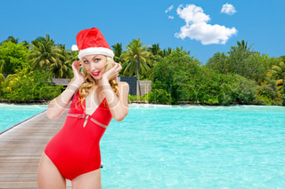 The girl in a bathing suit and a cap of Santa Claus against palm trees