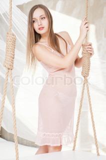 Beautiful woman on a swing in lingerie