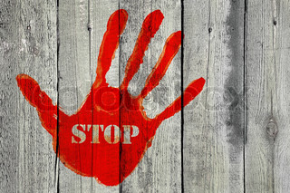 Handprint with the word ''Stop'' on old wooden fence background
