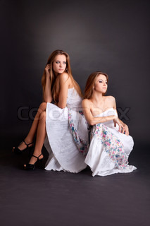 Two girls twins, isolated on the black background