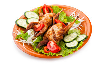 Two whole quail with cucumber, tomatoes and onion