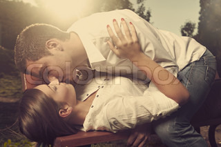 Loving young couple enjoying date in early autumn city park, kissing, touching and embracing each other