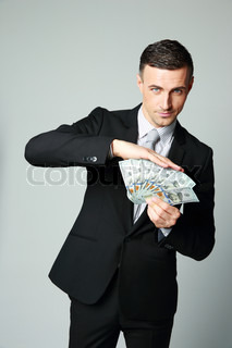 Businessman holding group of dollar bills on a gray background