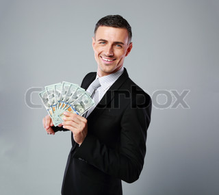 Cheerful businessman holding group of dollar bills on a gray background