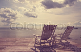 White wooden beach chair facing seascape,vintage filter effect