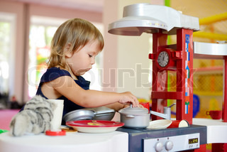 girl playing toy kitchen