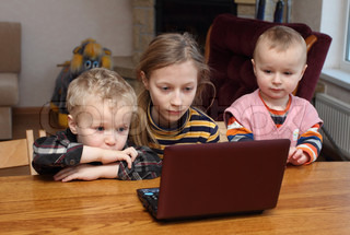 Children look at a computer
