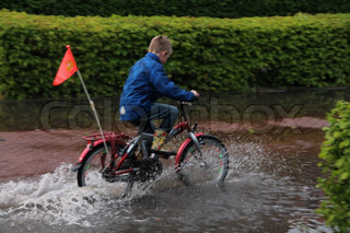 Flooding, the boy with the red bike and multicolored boots, makes splashing water in the pool for fun.