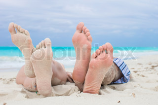 Close up male and female feet on white sand