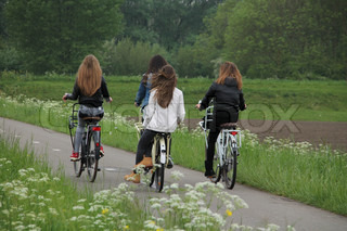 The girlfriends are biking along the roadside with blooming cow parsley and going home in spring.