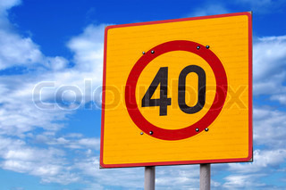 Speed limit road sign above blue cloudy sky
