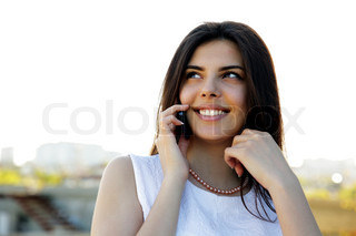Portrait of a beautiful cheerful woman speaking on the phone outdoors