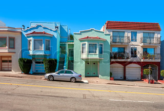 Colorful residential houses standing in row on sloping street of San Francisco, USA.
